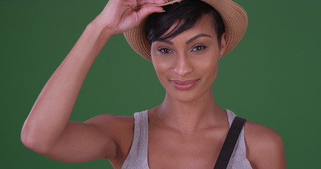 Happy smiling black woman holding hat on green screen