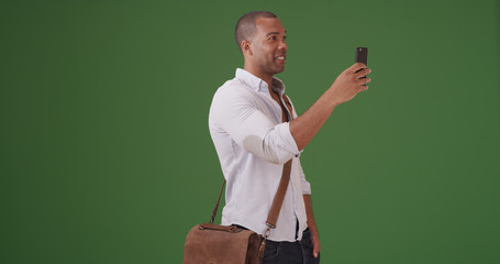 A young black man records video on his mobile phone on green screen