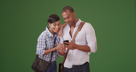 African American couple watching something on smartphone on green screen