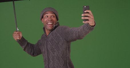 An African American man takes a selfie in the rain on green screen
