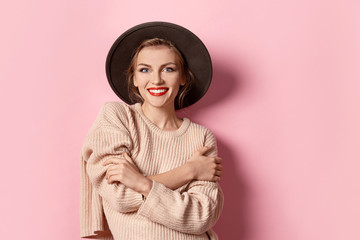 Portrait of fashionable girl wearing light  pullover on pink background. Stunning female with natural makeup and bright red lips. Youth concept. Wall mural