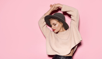 Portrait of woman posing wearing cosy sweater on pink background. Fashion photo shoot of naturally beautiful girl in trendy hat.