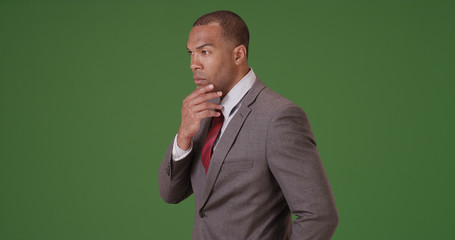 A black businessman thinking to himself on green screen