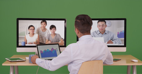 Business man having video conference with group of professionals on green screen