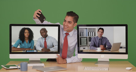Businessman during video conference taking selfie with phone on green screen