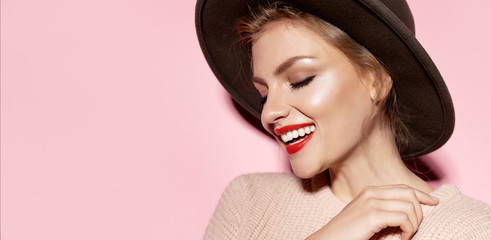 Wall Mural - Woman with natural makeup looking away and smiling on pink background. Youth and skincare concept