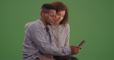 Black couple sit on a bench looking at their smart phone on green screen
