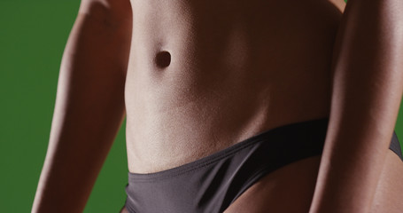 Closeup of woman's flat toned stomach on green screen