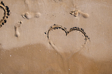 emblem of the heart of love is painted on the sea sand on a warm summer day next to the prints of human feet