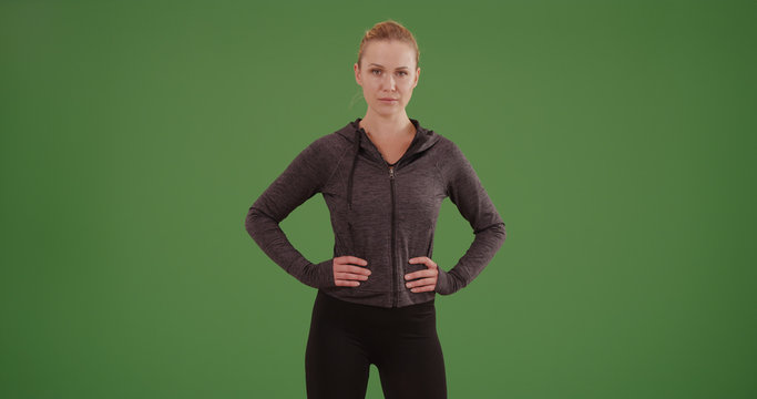 Confident woman athlete standing with hands at hips on green screen