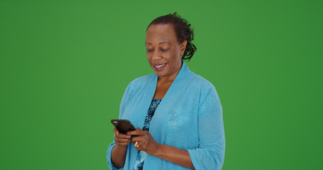 Black elderly woman uses smartphone to text on green screen
