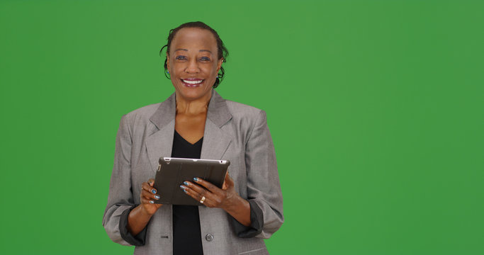 A black businesswoman using tablet smiling at camera on green screen