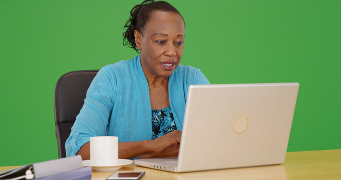 An African American office employee working on laptop on green screen