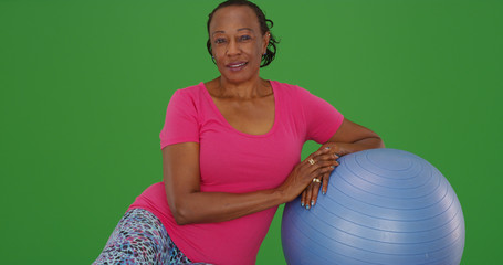 Healthy elderly back woman leaning on exercise ball on green screen