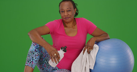 Active old black lady resting after workout on green screen