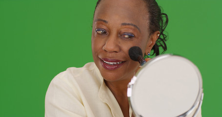 Senior African-American lady applying makeup on green screen