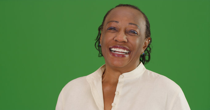 Happy mature black woman laughing on green screen
