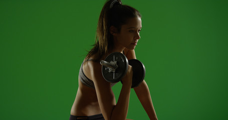 Young white woman works out while sitting down on green screen