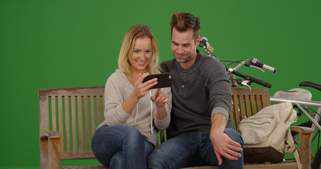 Happy couple on park bench watching videos on smartphone on green screen