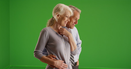 Old couple standing together looking at something offscreen on green screen