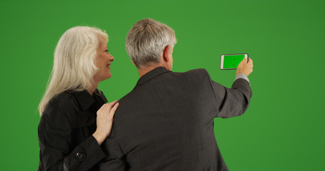 Senior couple using smartphone to take picture on green screen