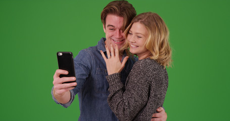 Happy engaged couple taking selfie with cellphone on green screen