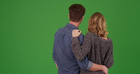 Rear view of sweet loving white couple holding each other on green screen