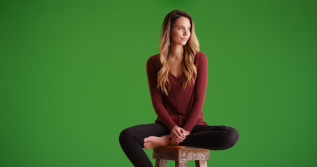 Attractive woman sitting on stool looking offscreen smiling on green screen