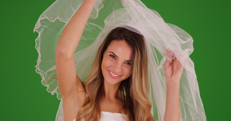 Beautiful bride revealing her face and laughing at camera on green screen Wall mural