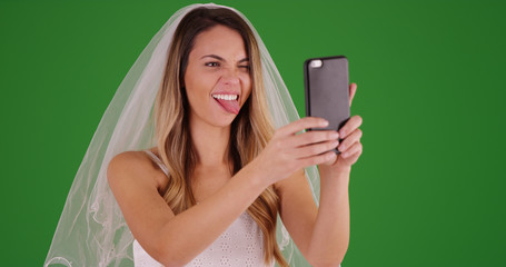 Young bride in wedding dress taking funny selfie with phone on green screen