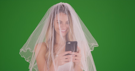 Bride in wedding dress and veil taking a selfie with smartphone on green screen