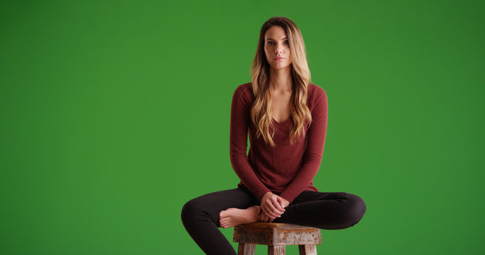 Female millennial sitting on stool looking at camera on green screen