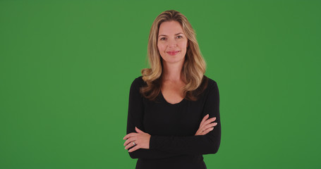 Attractive blonde middle aged woman smiling with arms crossed on green screen