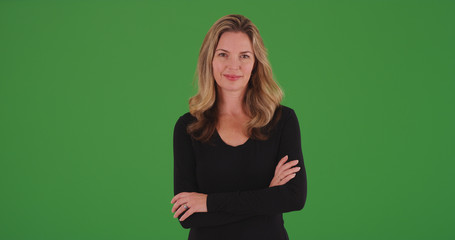 Attractive blonde female smiling at camera with arms crossed on green screen