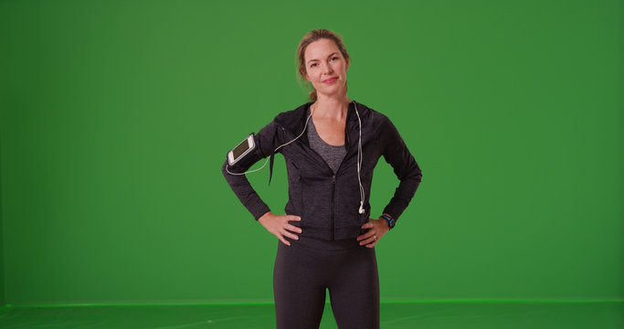 Athletic Caucasian woman in sportswear smiling at camera on green screen