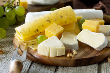 Various types of cheese on rustic wooden table.