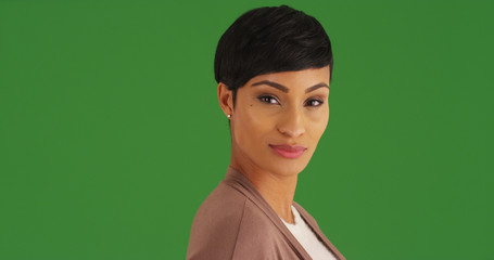 Confident African American female looking at camera on green screen