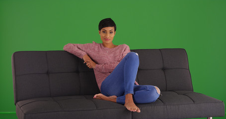Casual African-American woman sitting on sofa looking at camera on green screen