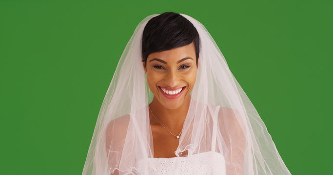 Closeup of happy bride in wedding dress smiling at camera on green screen
