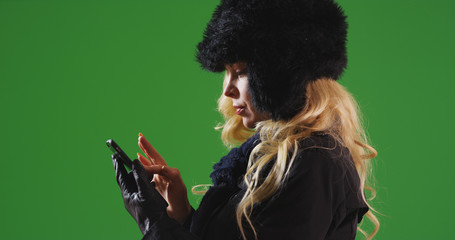 Caucasian woman in fur cap and scarf messaging on cellphone on green screen