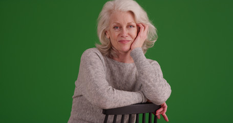 Portrait of old woman sitting in chair looking at camera on green screen