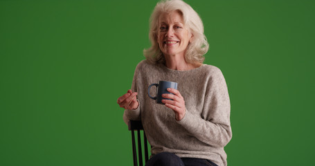 Happy mature white woman with coffee smiling at camera on green screen