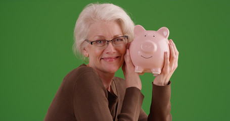 Charming mature white female posing with piggy bank on green screen
