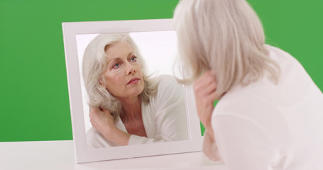 Elegant senior woman looking in mirror fixing her hair on green screen