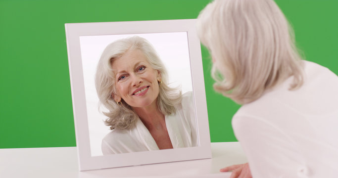 Beautiful Caucasian senior woman looking at mirror on green screen