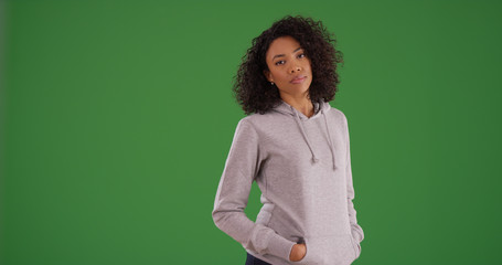 Young black female in gray hoodie with hands in pockets on green screen
