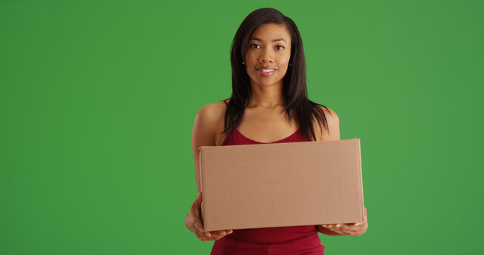 Smiling young black female holding cardboard box on green screen