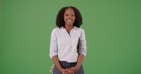 Cheerful black female gardener smiling at camera on green screen