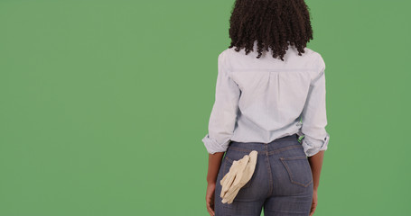 Rear view of black female with gardening gloves in back pocket on green screen