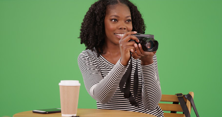 African American female with camera about to take photo at cafe on green screen